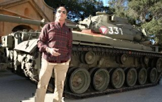 arnold-schwarzenegger-standing-in-front-of-his-tank